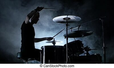 Energetic musician plays good music on drums. Black smoky background . Side view. Silhouette. Slow motion