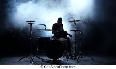 Energetic musician plays good music on drums. Black smoky...