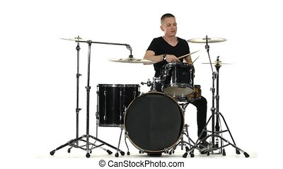 Energetic professional musician plays good music on drums. White background
