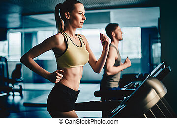 Energetic run - Active female running on treadmill in gym...