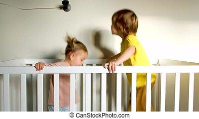 Energetic siblings jumping in crib - Side view of little boy...
