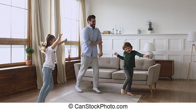 Energetic small kids siblings having fun with father.