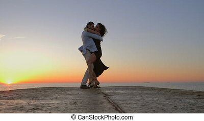 Energetic spanish couple against the background of the sunrise and ocean demonstrates elements of sensual Latin dance: bachata, rumba or kizomba. Slow motion