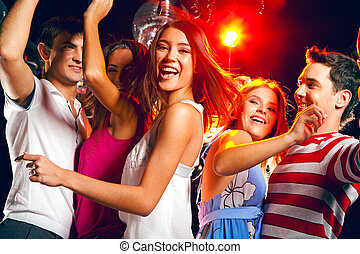 Energetic teenager - Pretty clubber dancing surrounded by...