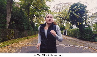 Energetic Woman Running on Road - Young energetic woman...