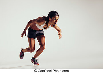 Energetic young woman running over grey background. Focused...