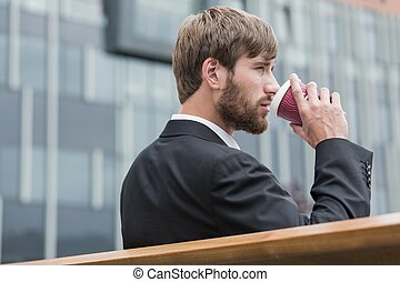Young businessman sitting on a bench and drinking beverage