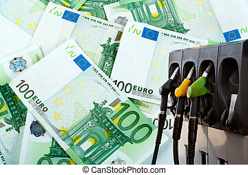 Energy and money - Three gas pump nozzles over a money...