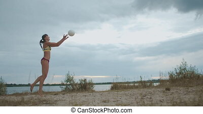 energy and power of sportswoman at volleyball match on beach, slow motion shot, female player is serving ball into play