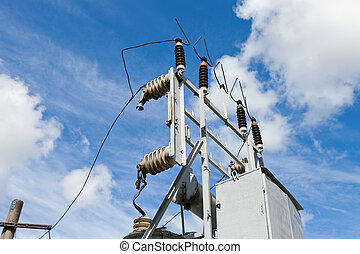 Energy and technology: electrical post by the road with power line cables, transformers against bright blue sky providing copy space.