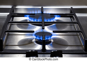 Energy Concepts. Closeup Shoot of Gas Burner on Stove Surface with Fire Flames.