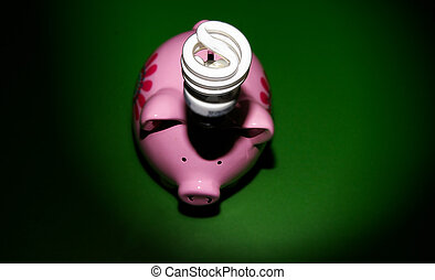 Energy efficient light-bulb over a piggy bank, on green