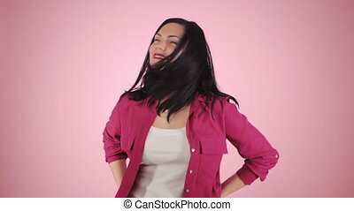 Energy girl on pink background in studio. She wears colorful...
