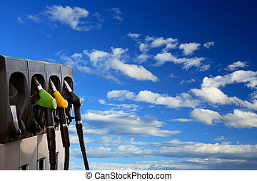 Three gas pump nozzles over a sky background