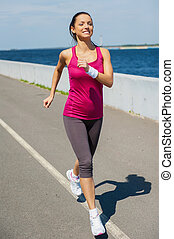 Energy inside her. Full length of beautiful young woman running along the road and smiling