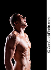 Energy inside him. Side view of handsome young shirtless man shouting and keeping eyes closed while standing against black background