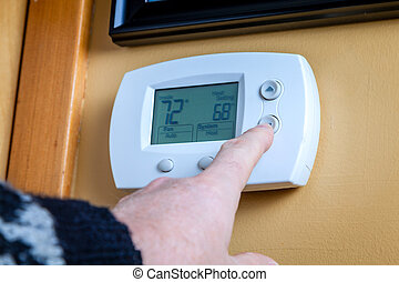 Energy saving - A person lowers temperature on a home ...