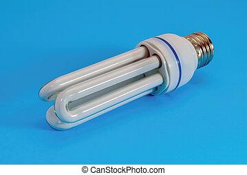 Energy saving fluorescent light bulb close-up on a blue background.