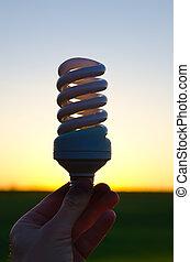 energy saving lamp in hand over sunset