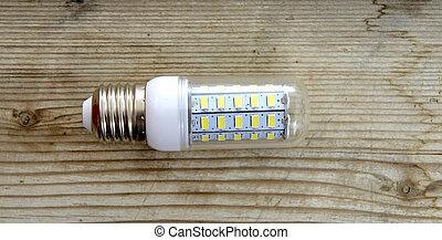 Energy saving LED light bulb on a wood background