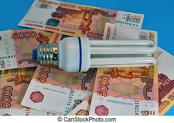 Energy saving light bulb close-up on a background of banknotes.