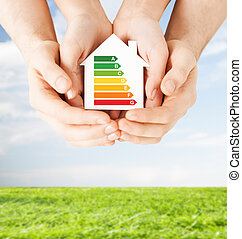 hands holding white paper house - energy saving, real estate...