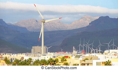 Energy wing power turbine rotates on sunset mountains...