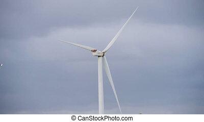 Energy wing power turbine rotates on sunset sky background....