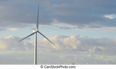 Energy wing power turbine rotates on sunset sky background. ...