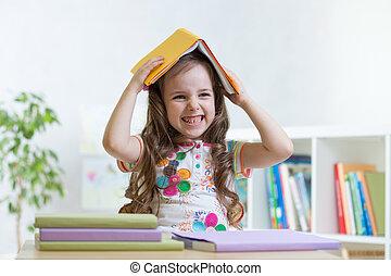 enfant, étudiant fille, dans, les, école, tient, a, livre, sur, elle, tête