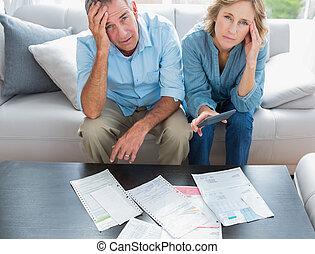 enfatizado, pareja, sentado, en, su, sofá, pagar, su, cuentas