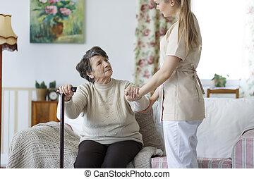 enfermeira, ajudando, mulher idosa, estar pé, cima