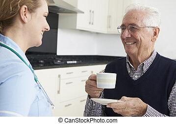 enfermeira, conversando, com, homem sênior, durante, visita...