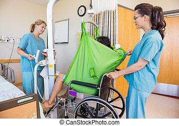 enfermeras, transferir, paciente, de, elevador hidráulico, a, sílla de ruedas