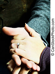Newly engaged couple holding hands with the engagement ring showing.