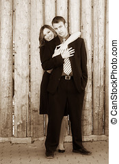 Engaged couple standing in front of a wooden wall.