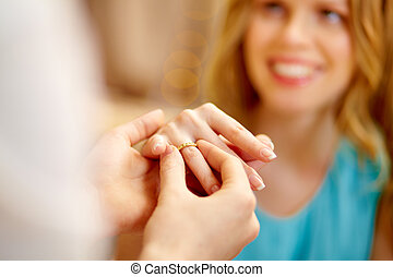 Guy putting an engagement ring on the finger of his girlfriend