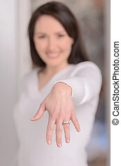 Engaged woman. Beautiful young woman showing her hand with an engagement ring on the finger