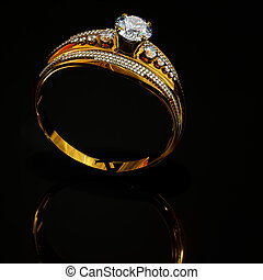 Engagement gold ring with jewelry diamond gem on surface reflection .