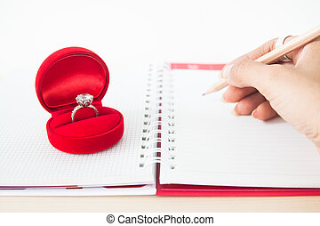 Engagement or Wedding ring in red box with woman's hand writing on notebook, Love and Valentine's Day