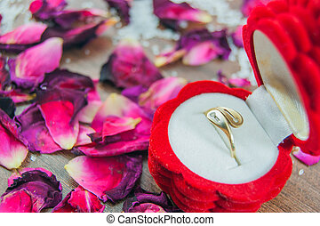 Engagement ring in a box, rose petals