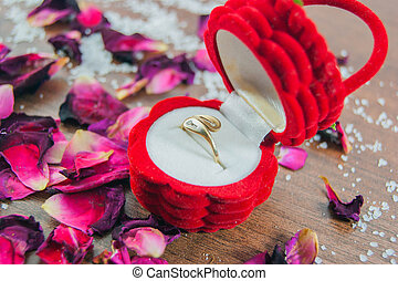 Engagement ring in the red box, rose petals - focus ring