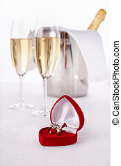 Wine Glasses with champagne and Engagement Ring, selective focus on nearest