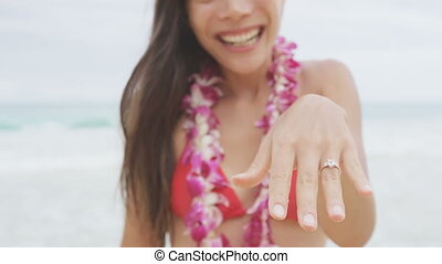 Engagement ring. Woman showing Engagement ring on beach after marriage proposal. Excited cute girl in wedding concept on Hawaii wearing flower Lei during holiday travel. RED EPIC SLOW MOTION