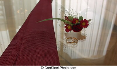 engagement rings, tie and boutonniere glass table groom before the ceremony