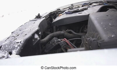 Engine compartment of the car in the winter, it is snowing,...