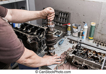 Engine crankshaft, valve cover, pistons. mechanic repairman at automobile car engine maintenance repair work