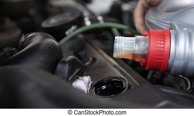 Engine lubrication - Close up of pouring motor oil...
