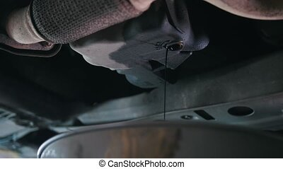 Engine oil under bottom of the car in garage workshop, close...