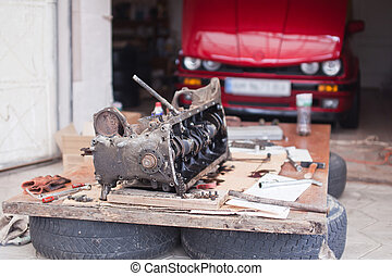 Engine repair, which lies on the background of a red car